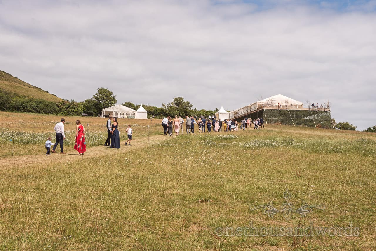 Wedding guests walk up countryside hill for drinks reception and Purbeck marquee wedding photographs