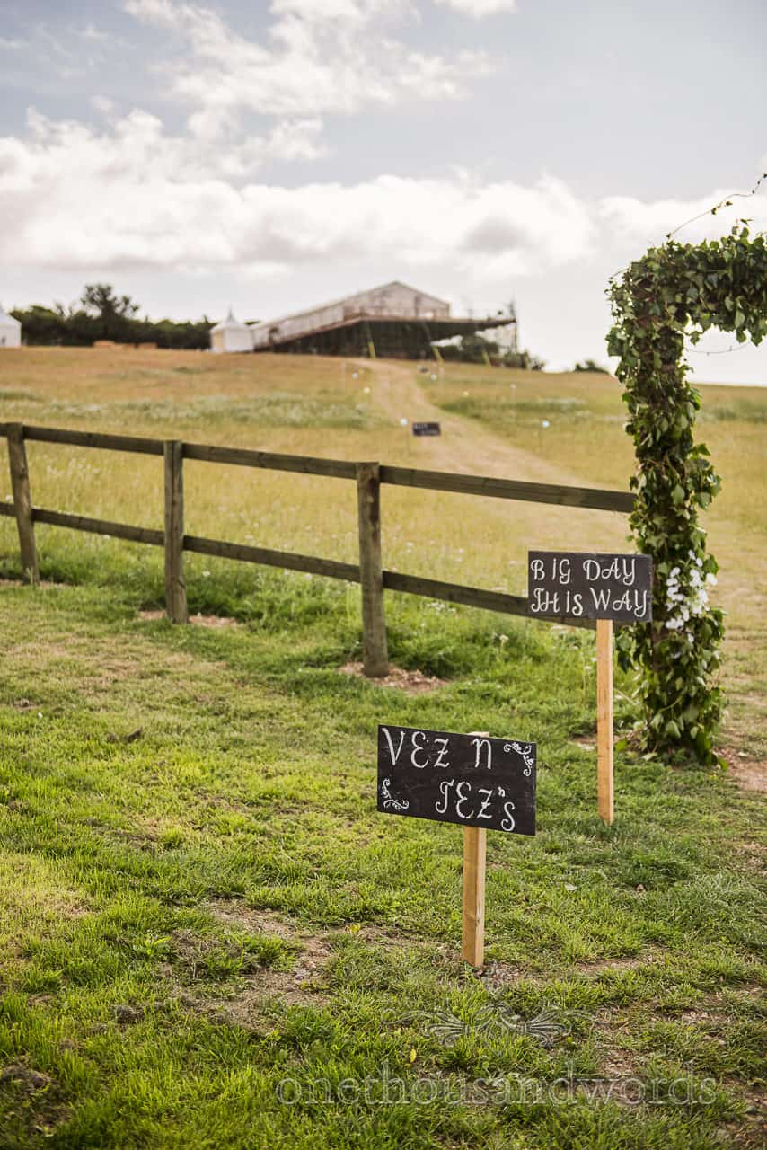 Chalk board wedding sign posts with grass filed hill leading to Purbeck marquee wedding photographs