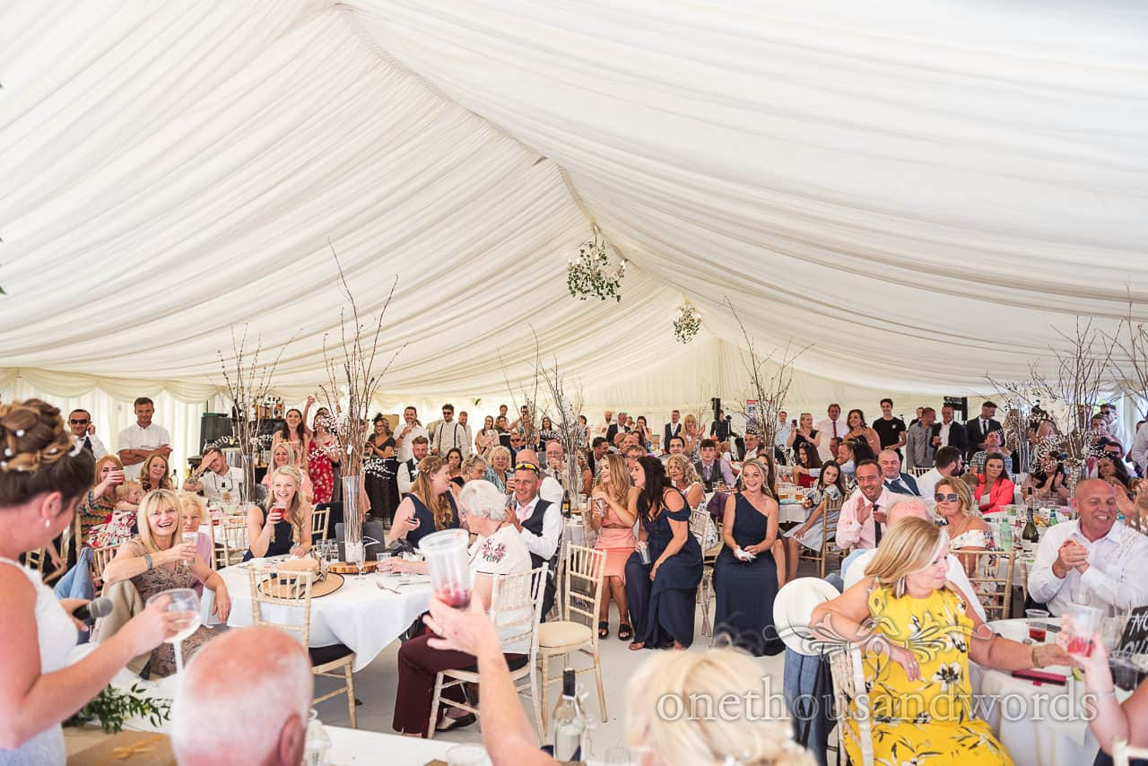 Purbeck marquee wedding photographs of happy guests listening to bride's wedding speech