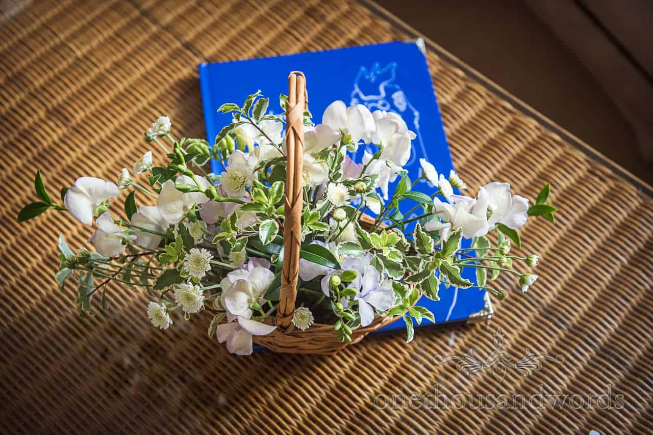 White wedding flower basket on wicker table with blue wedding book for flower girls detail photograph