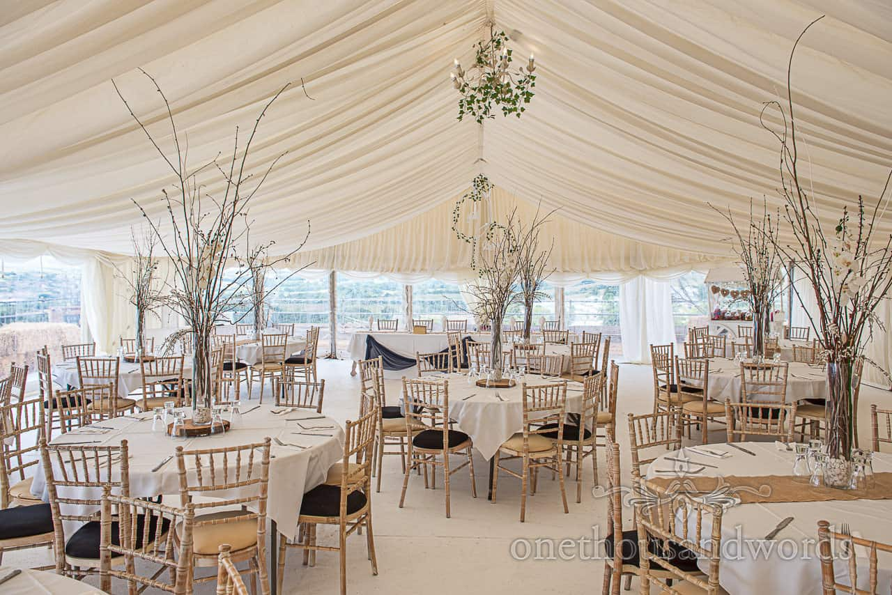 Round tables, cherry blossom and ceiling chandeliers decoration for Purbeck marquee wedding photographs