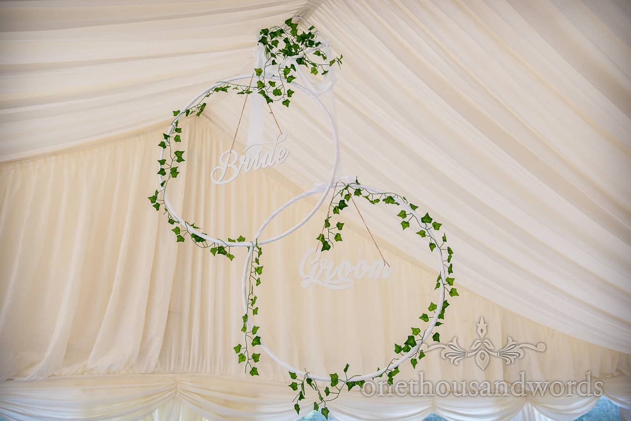 White bride and groom script hoops with ivy decoration hanging in wedding marquee
