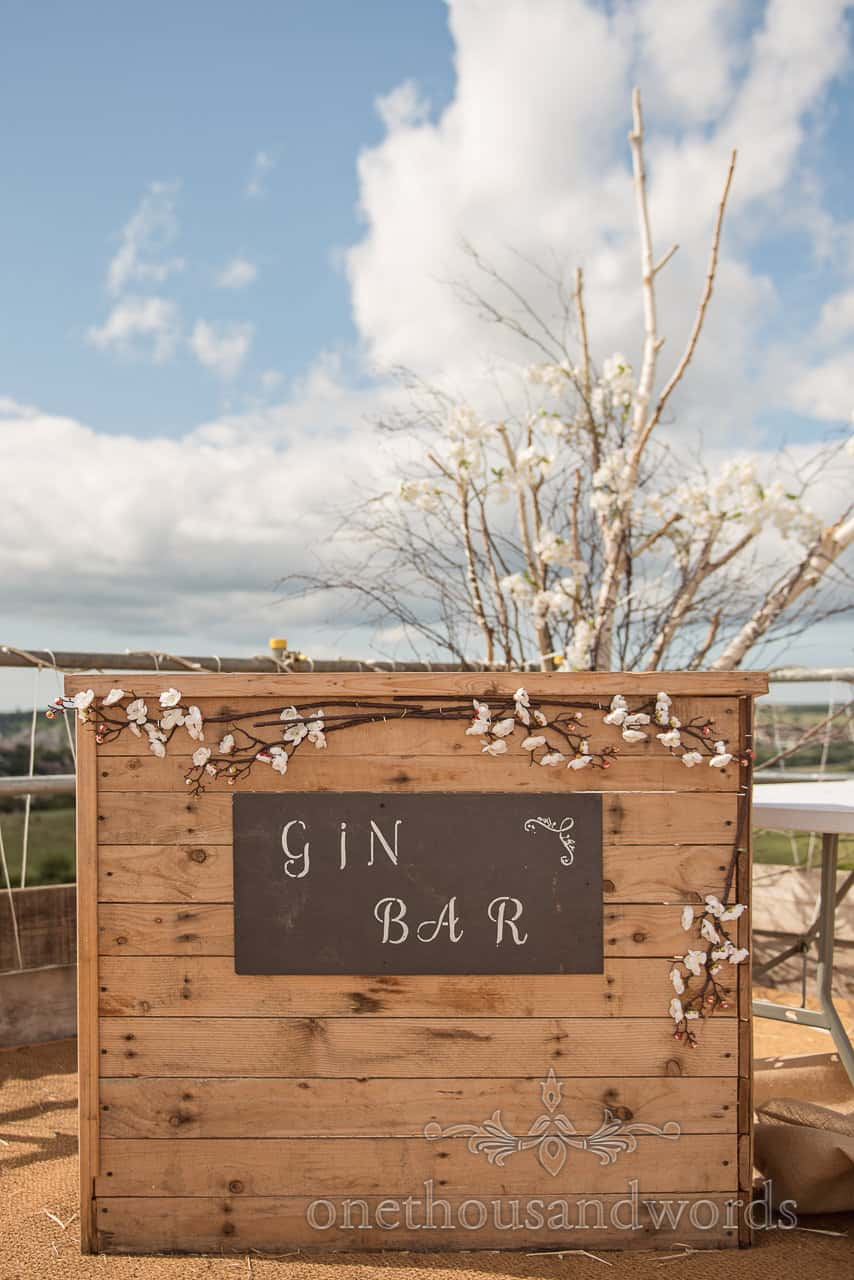 Wooden wedding gin bar with tree branch cherry blossom floral decoration and blue summer sky
