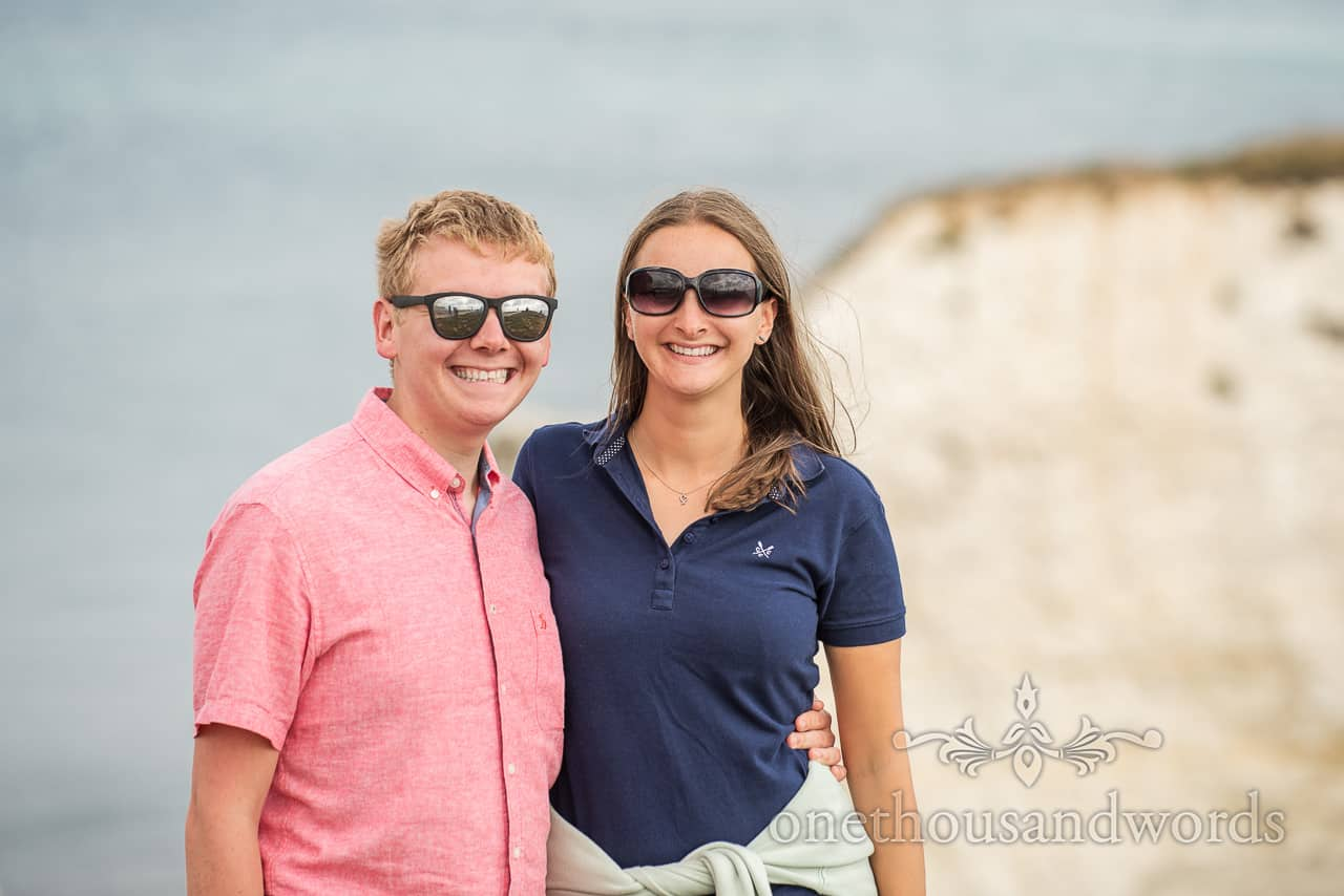 Dorset engagement photograph with couple wearing sunglasses against white coastal cliffs and sea backdrop by one thousand words