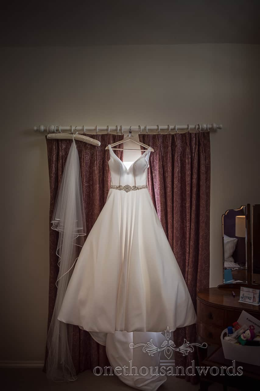A line wedding dress hangs In window on wedding morning at Athelhampton House cottage by one thousand words photography
