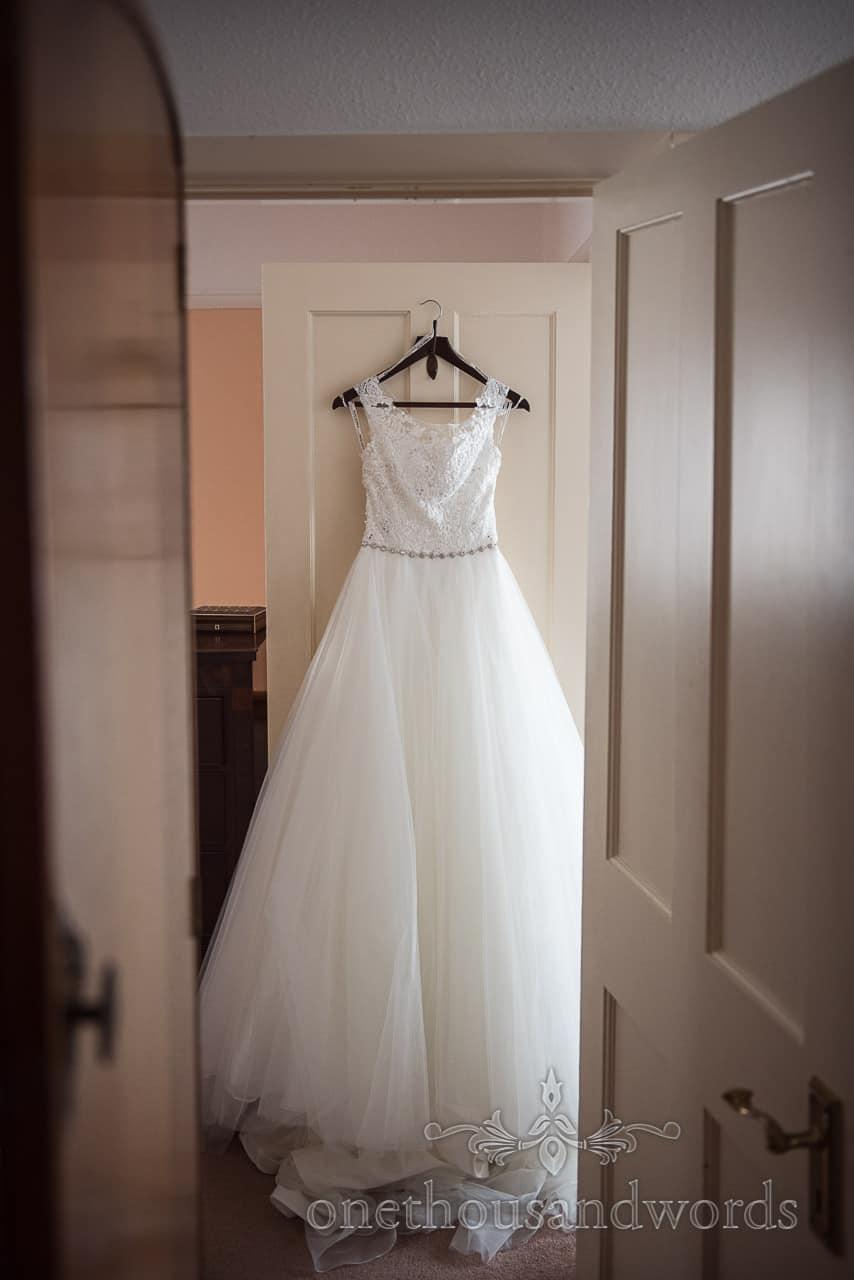 Bridal preparation detail wedding photograph of A line white wedding dress hanging on back of door