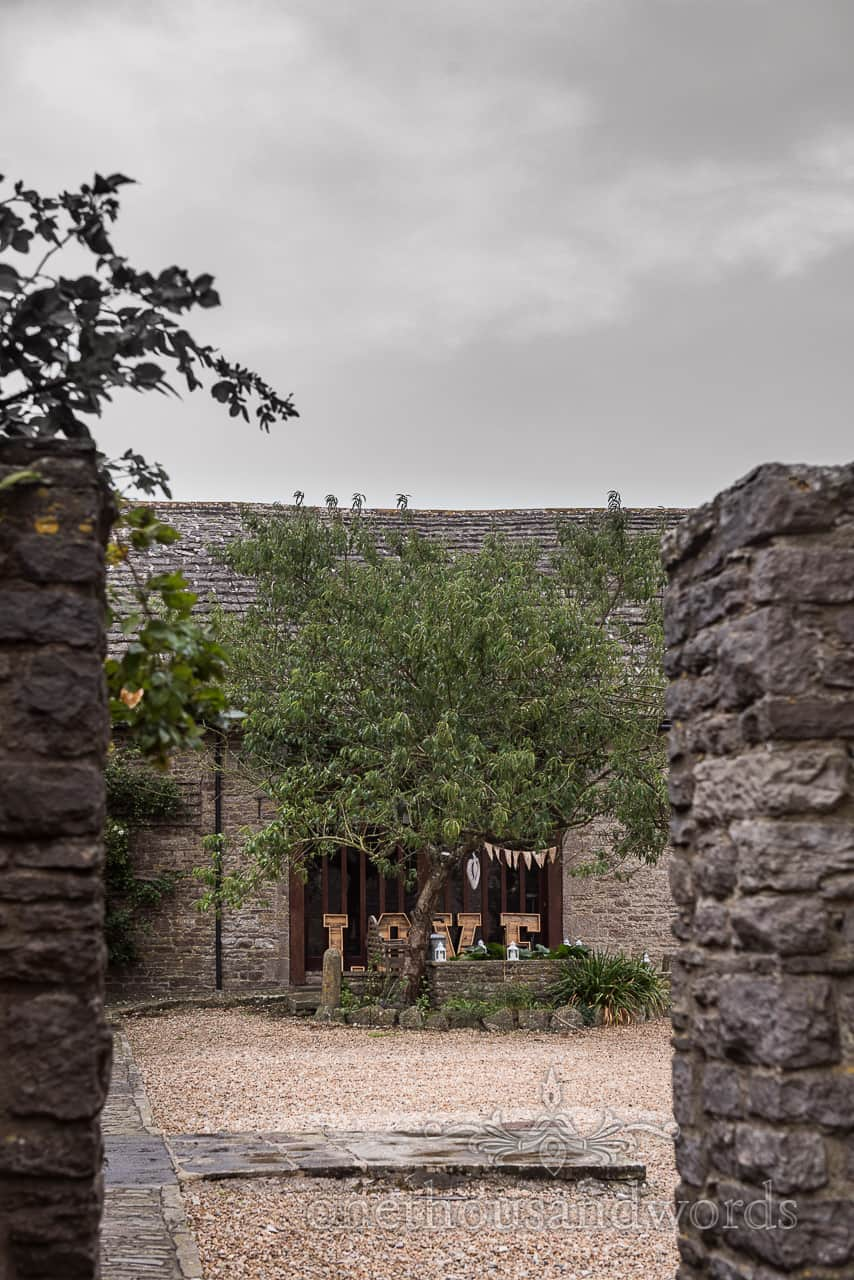 Photograph taken across Kingston Country Courtyard of giant wooden LOVE letters and bunting under a tree on a rainy wedding day