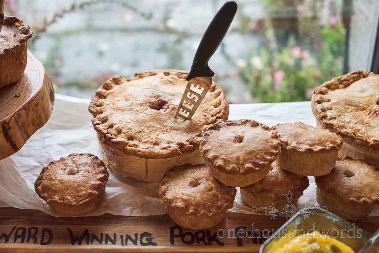 Award winning home made pork pies of different sizes with cheese knife displayed ready for evening wedding reception food