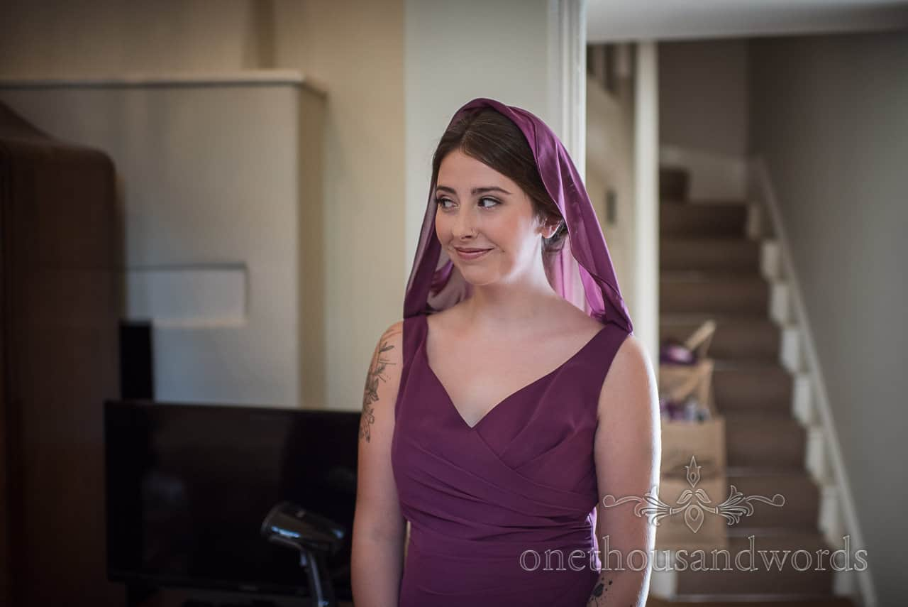 Berry coloured bridesmaid uses dress as mini cloak hood on wedding morning by one thousand words photography