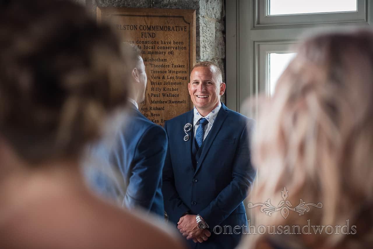 Happy best man wears three piece blue wedding suit and Refinerii Bridal metal titanium buttonhole boutonnière