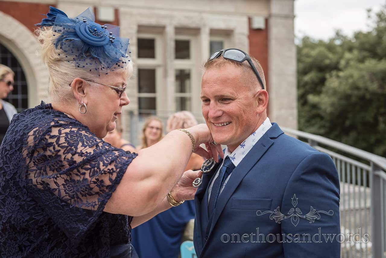 Best Man has buttonhole fastened before Purbeck castle wedding