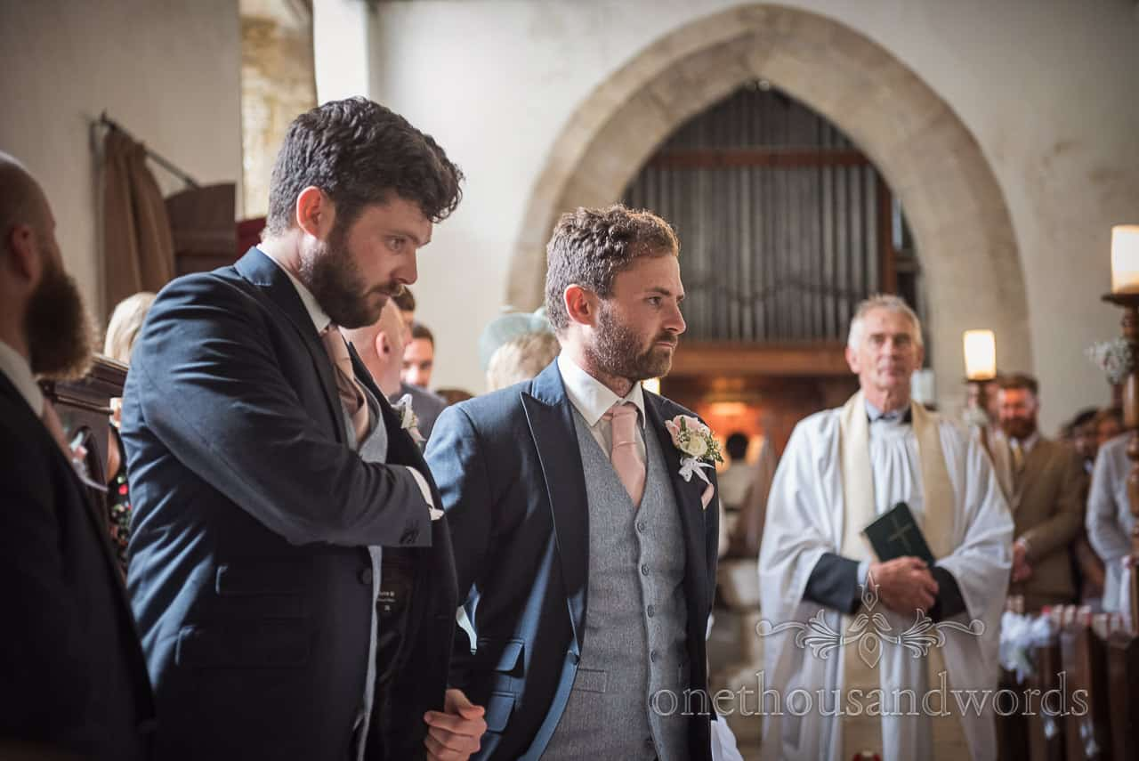 Best man checks his inside pocket for wedding rings as the groom waits for the bride to arrive at their church wedding ceremony