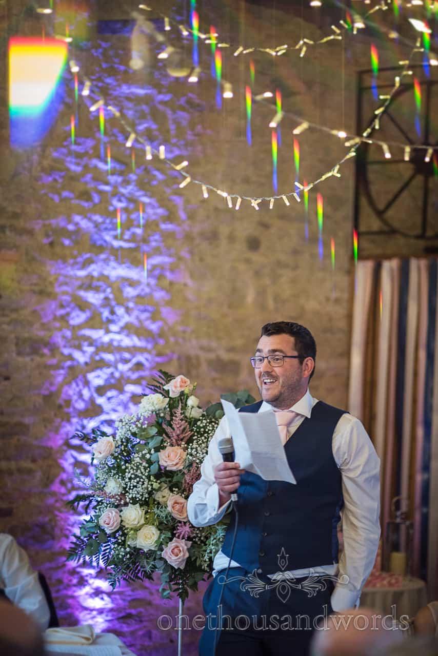 Best man reads wedding speech using a microphone under refracted fairy lights from Kingston barn wedding photographs