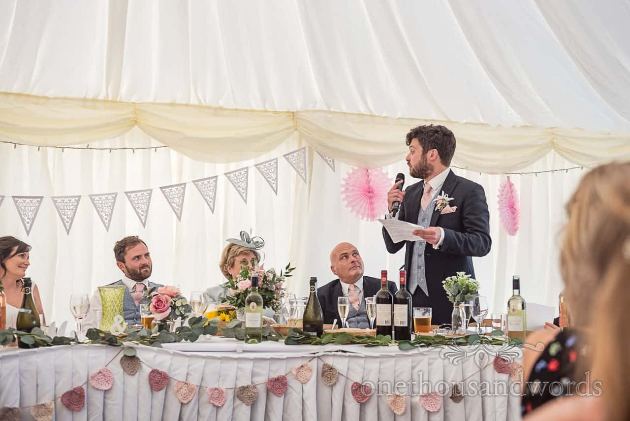 Best man in black suit delivers his wedding speech holding notes and microphone to top table at rustic marquee wedding