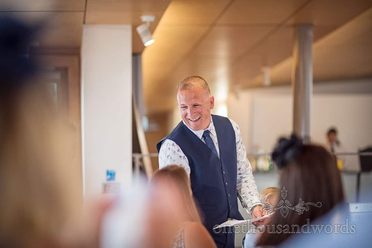 Best man in blue waistcoat and tie laughs during wedding speech photograph by one thousand words wedding photography