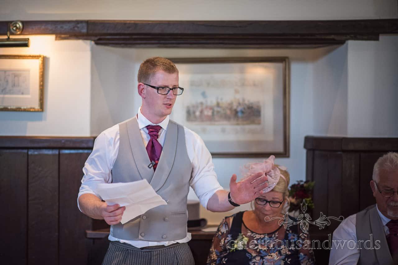 Best man in grey waistcoat and purple tie makes wedding speech during wedding breakfast