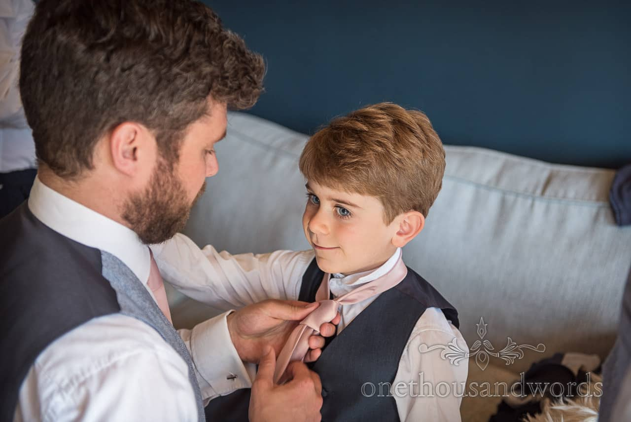 Best man helps page boy son with pink tie during wedding morning preparation photographs