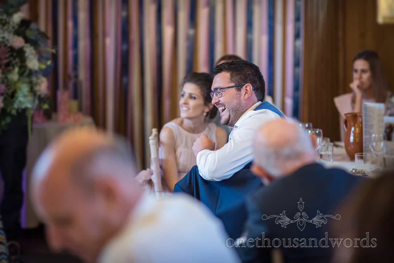 Best man's laughing reaction to wedding speeches at Kingston Country Courtyard Dorset barn wedding photographs