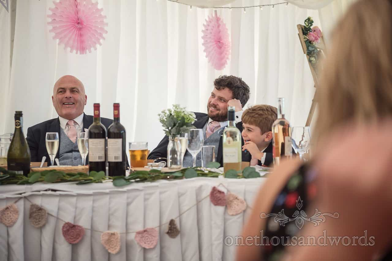 Father of the groom, best man and page boy laugh at wedding speeches sat at top table in wedding marquee