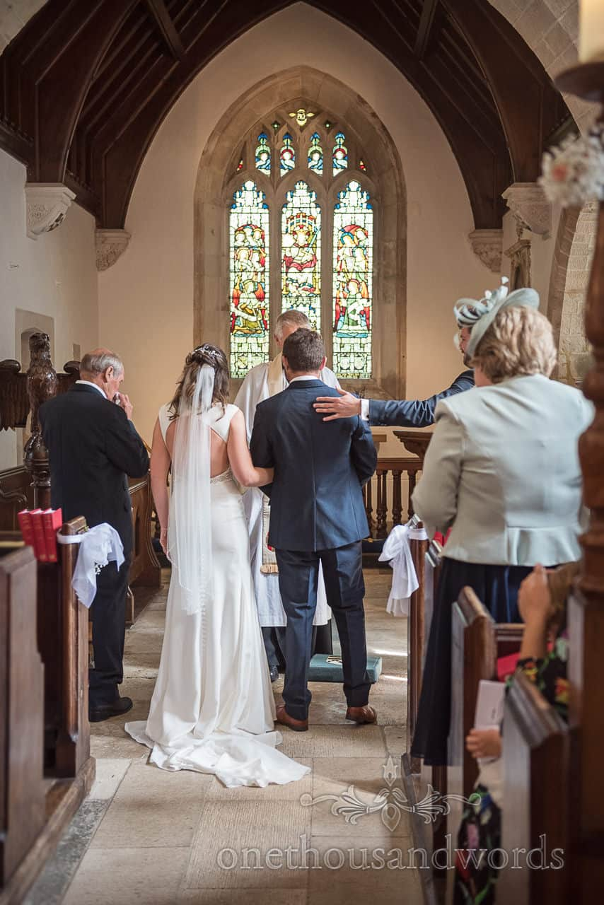 Best man reassures groom with pat on the back during Dorset stone church wedding ceremony photograph
