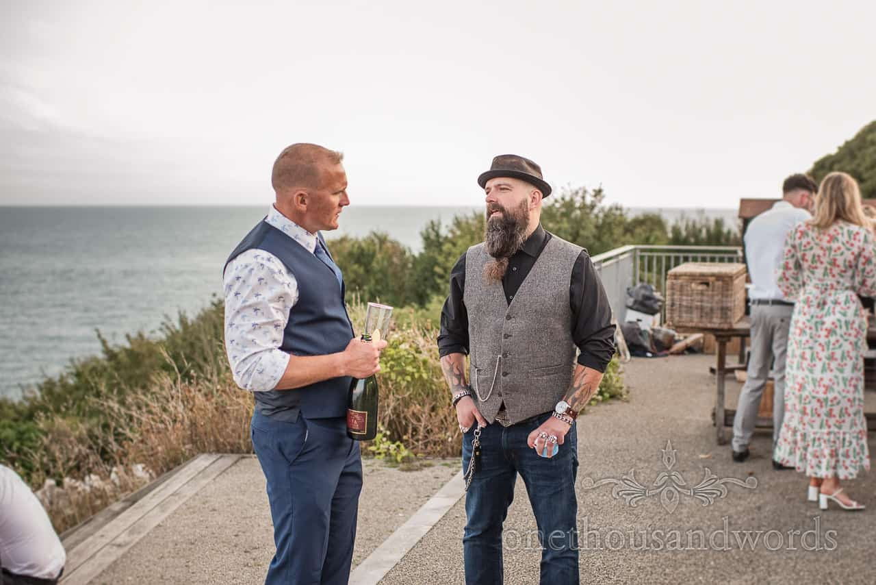 Best Man talks to bearded guest at Purbeck castle wedding reception