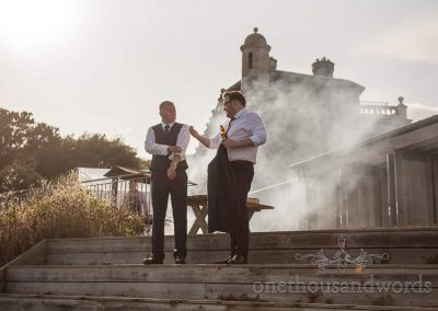 Best man and guest chat in front of smoking hog roast at Purbeck castle wedding
