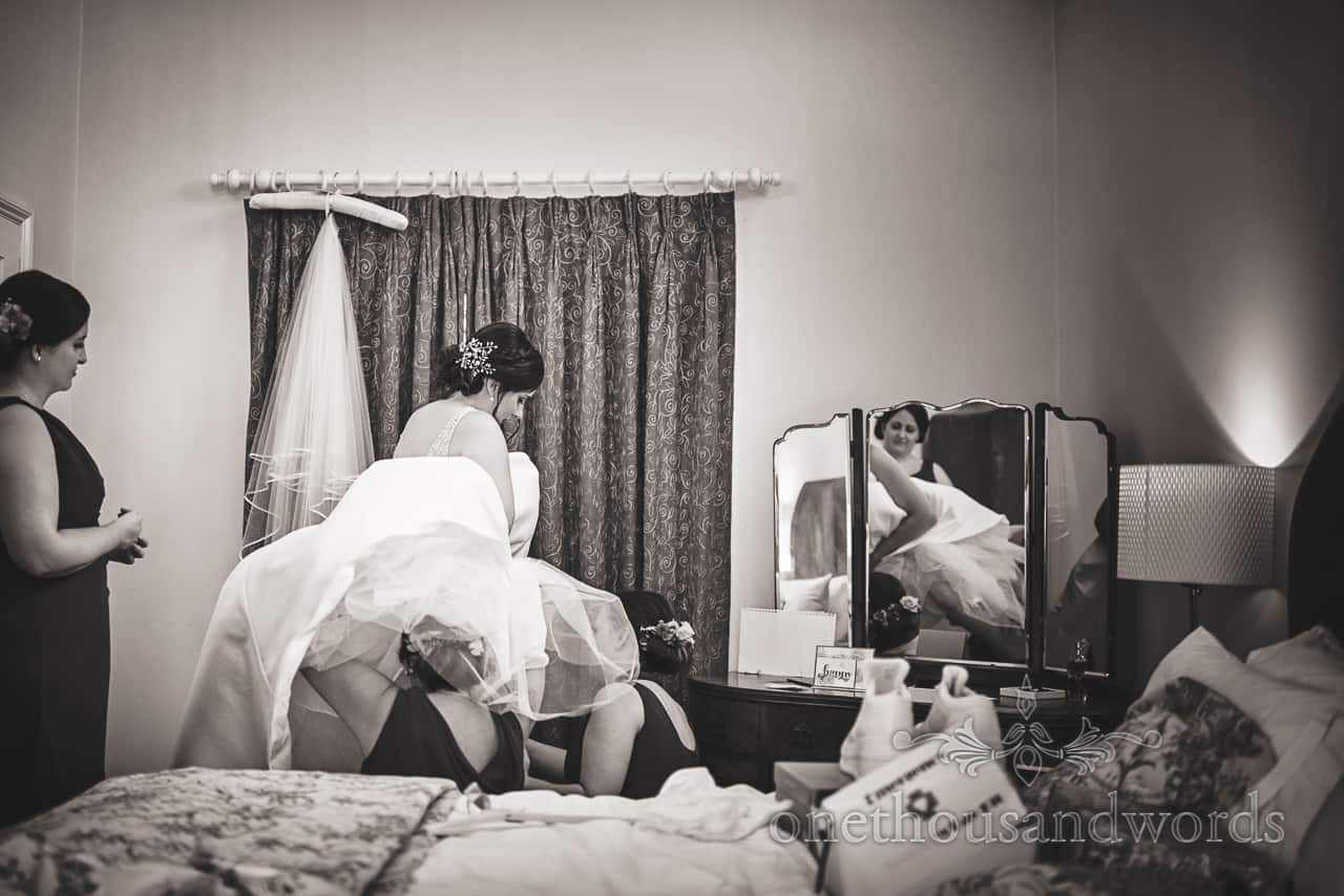 Black and white documentary photograph of bride helped into wedding dress by bridesmaids under dress