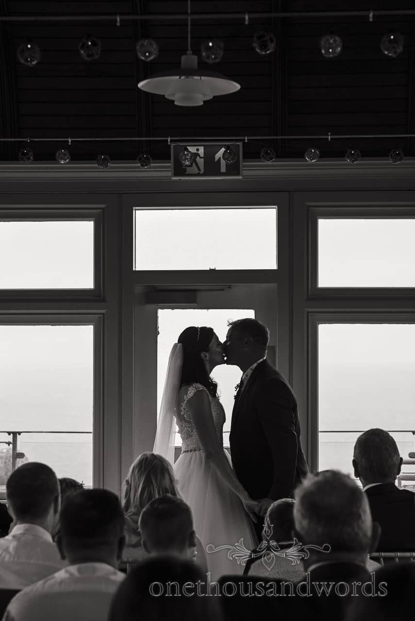 Black and white bride and groom first kiss silhouetted against windows documentary wedding photograph