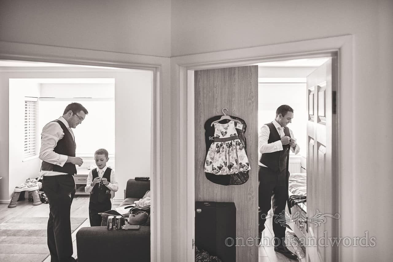 Black and white documentary wedding photograph of mirrored groomsmen in doorways on wedding morning by one thousand words