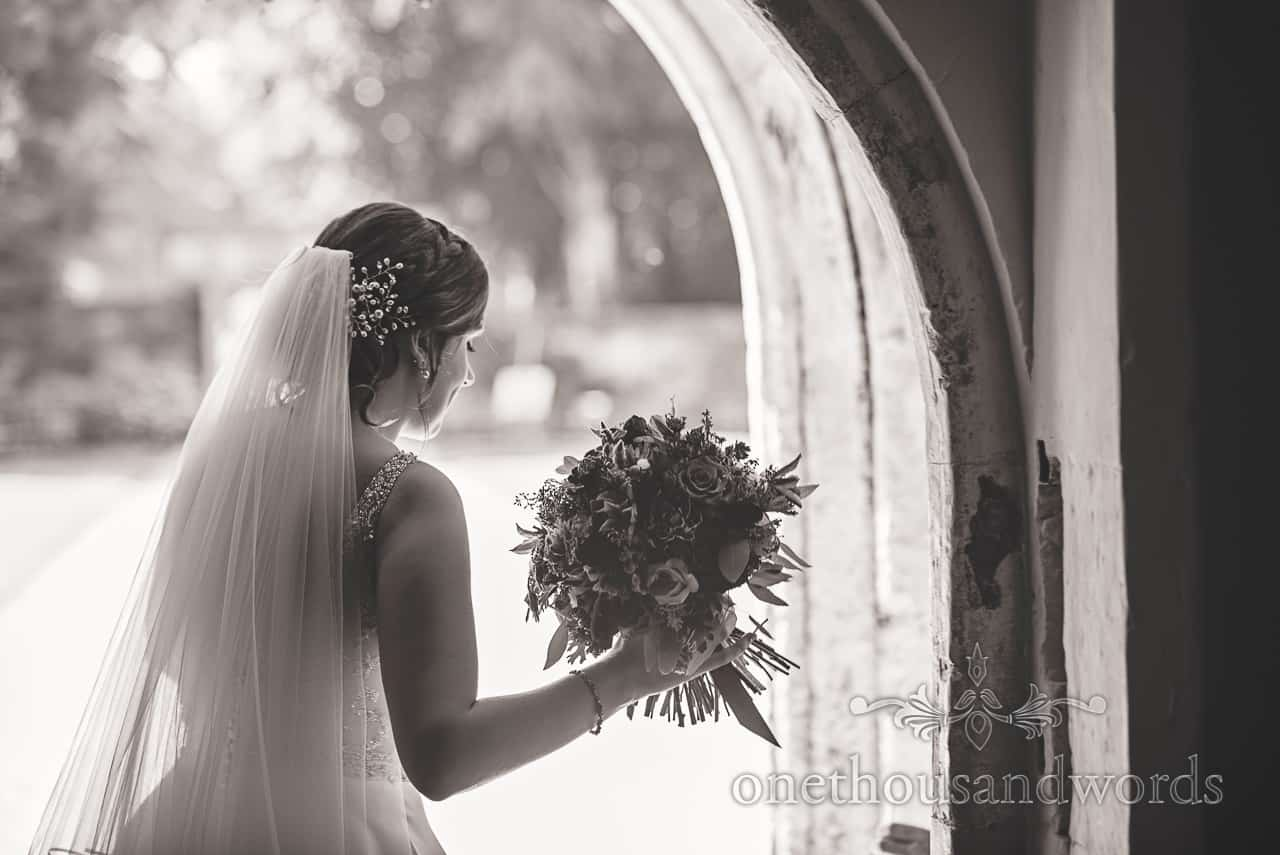 Black and white wedding photograph of bride with bouquet in stone doorway by one thousand words photography