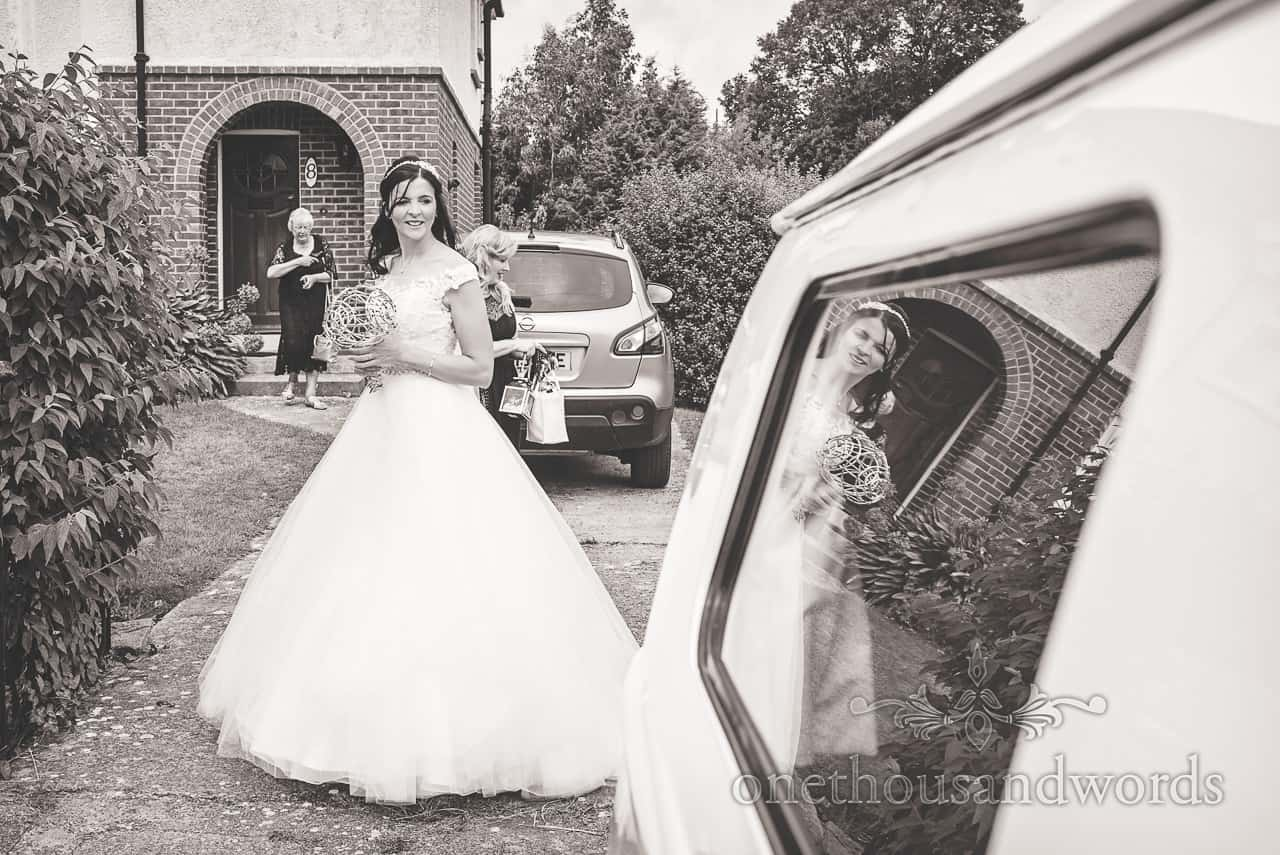 Black and white wedding photograph of bride and reflection in VW camper van by one thousand words documentary wedding photography in Dorset