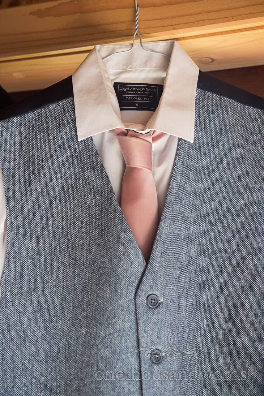 Wedding detail photograph of groom's blue woollen wedding waistcoat hanging with white shirt and pink tie