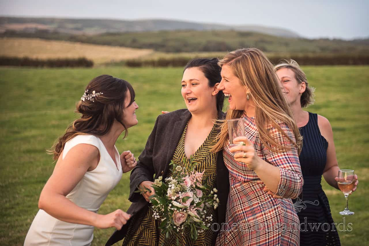 Bride and friends congratulate happy wedding guest that caught the wedding bouquet in countryside field