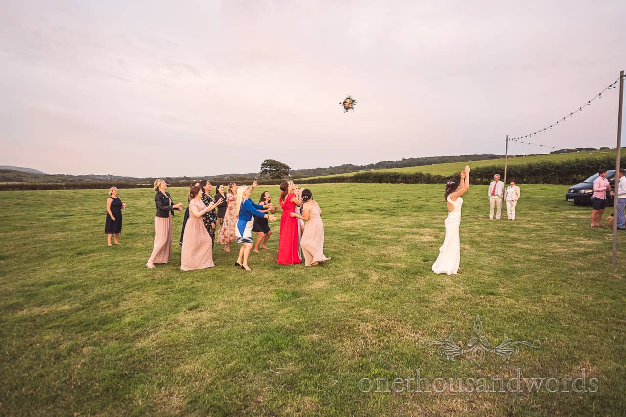 Bouquet toss wedding photograph taken from the side at a Purbeck farm wedding in a Dorset countryside field