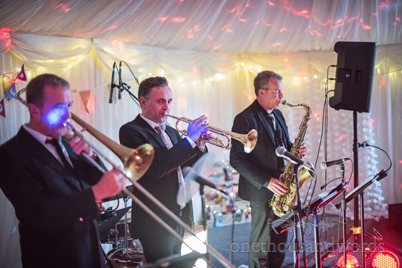Brass band playing wedding evening music in disco lights at a Purbeck farm marquee wedding photographs by one thousand words