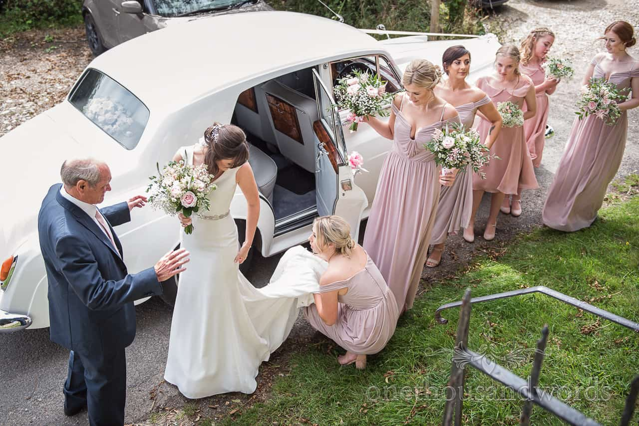 Bridesmaids bride and father with vintage wedding car and floral bouquets wait outside Dorset church wedding venue