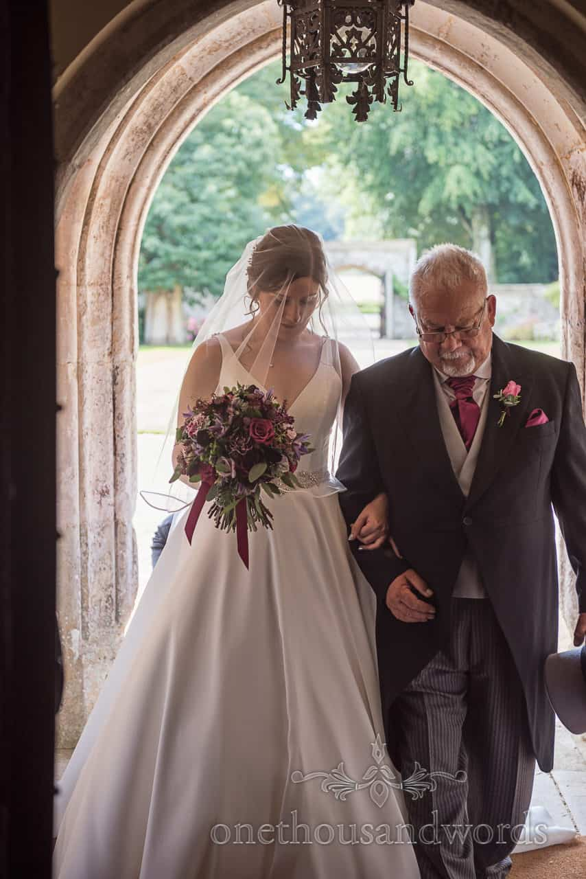 Bride and father in stone doorway at Athelhampton wedding ceremony by one thousand words photography