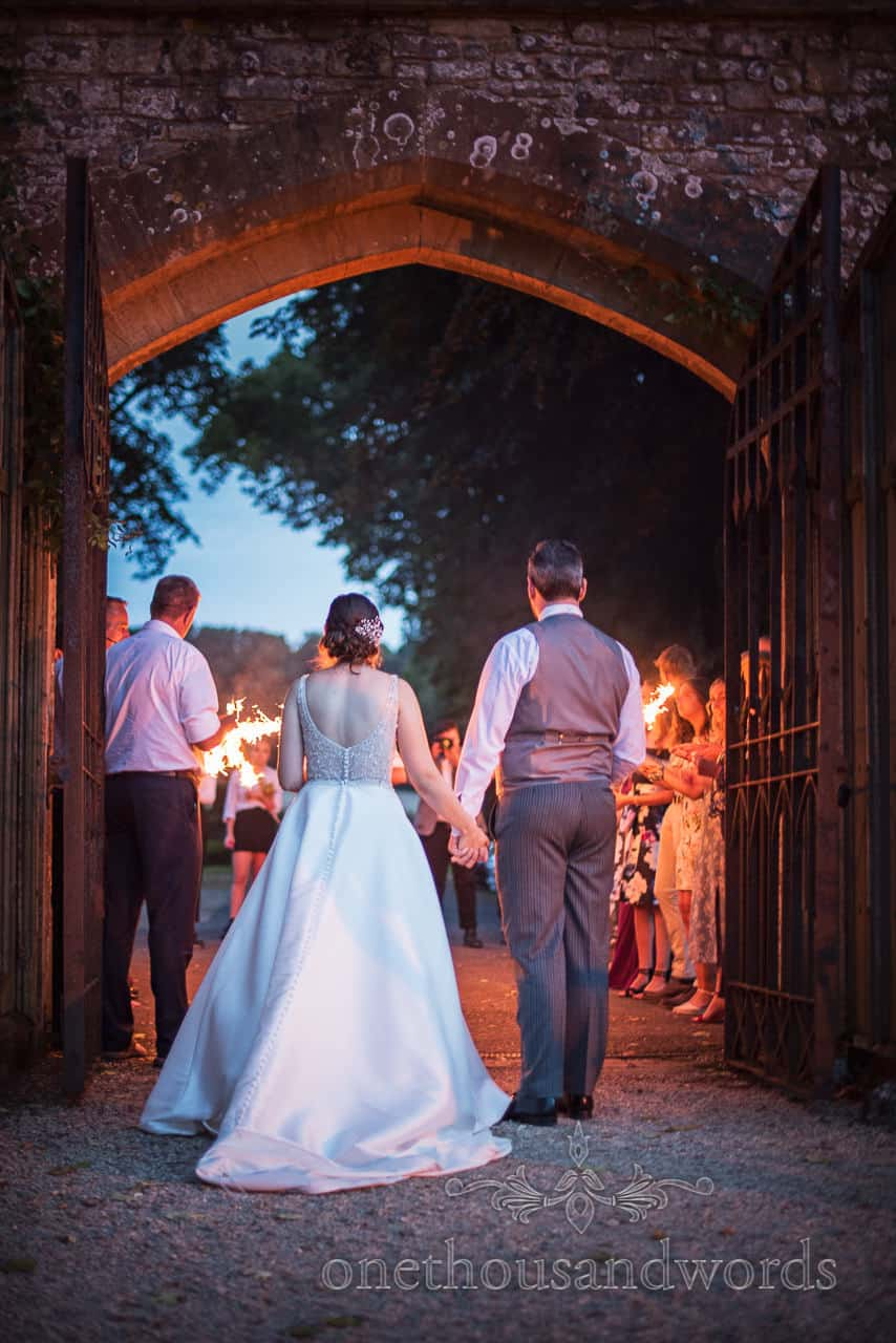 Bride and groom hold hands during sparklers photographs behind Athelhampton House gateway by one thousand words photography