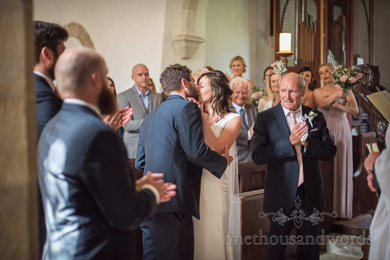 Bride and groom first kiss as wedding party and guests applaud during Dorset church wedding ceremony photographs
