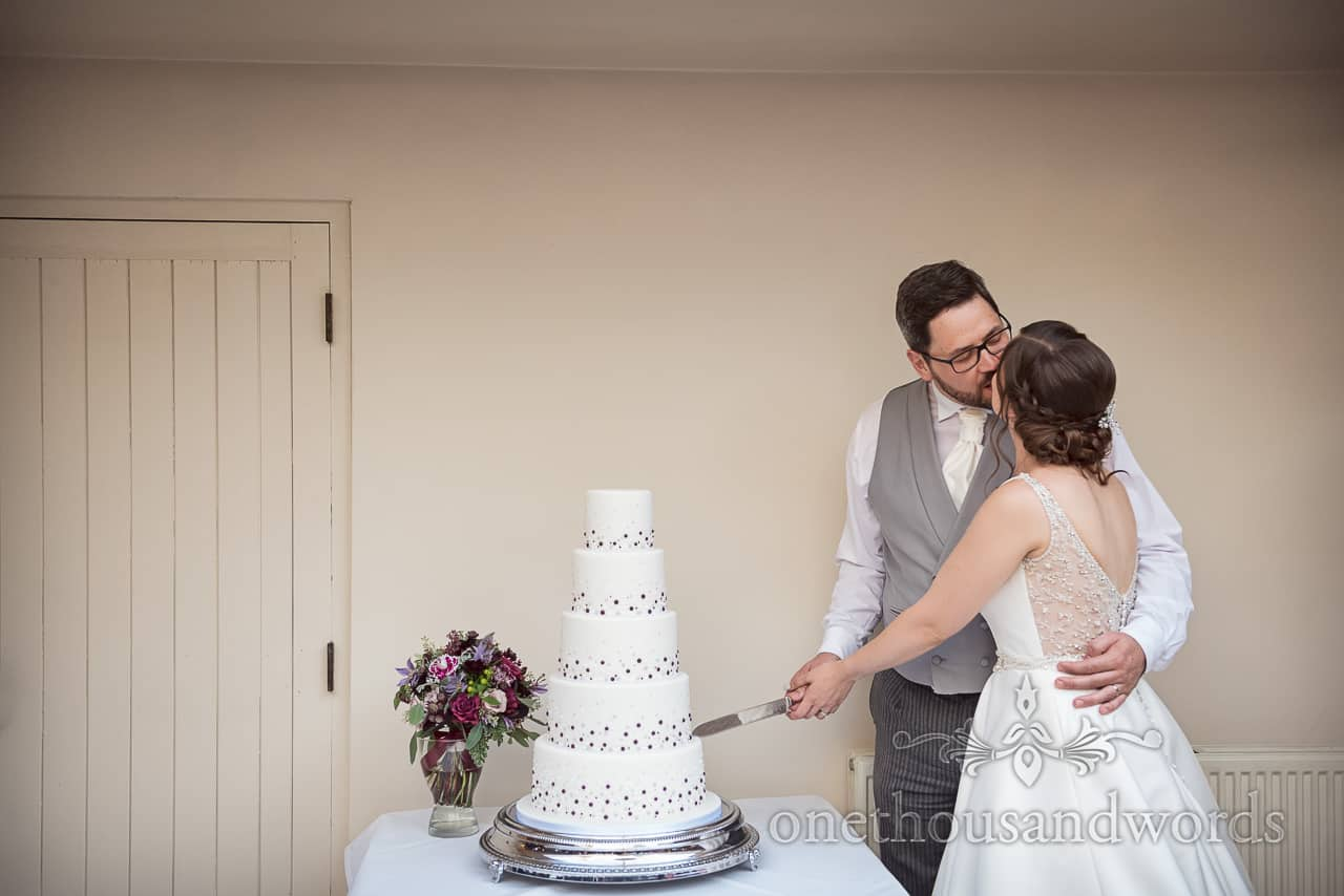 Bride and groom cut five tier wedding cake at Athelhampton Coach House reception by one thousand words