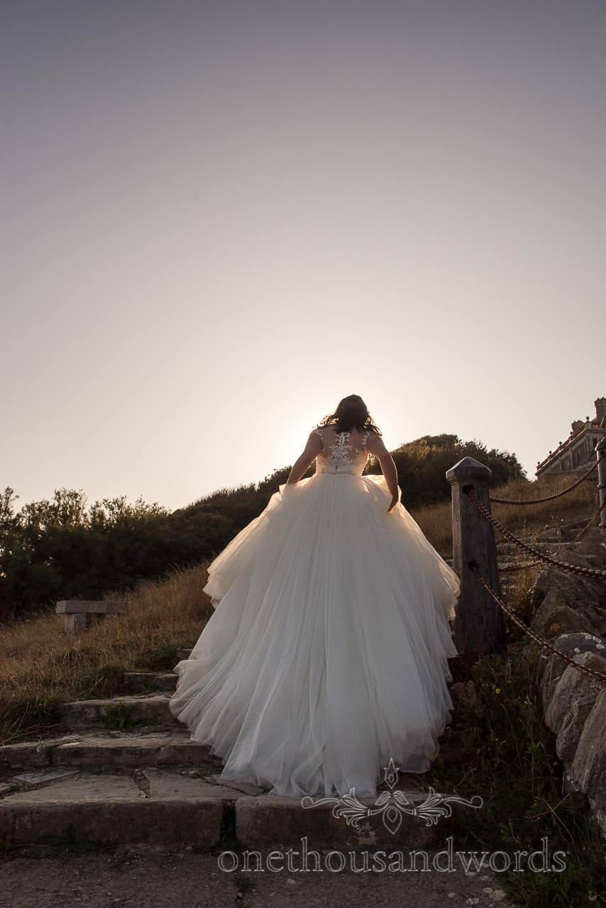 Bride ascending stone stairs from Purbeck castle wedding photographs