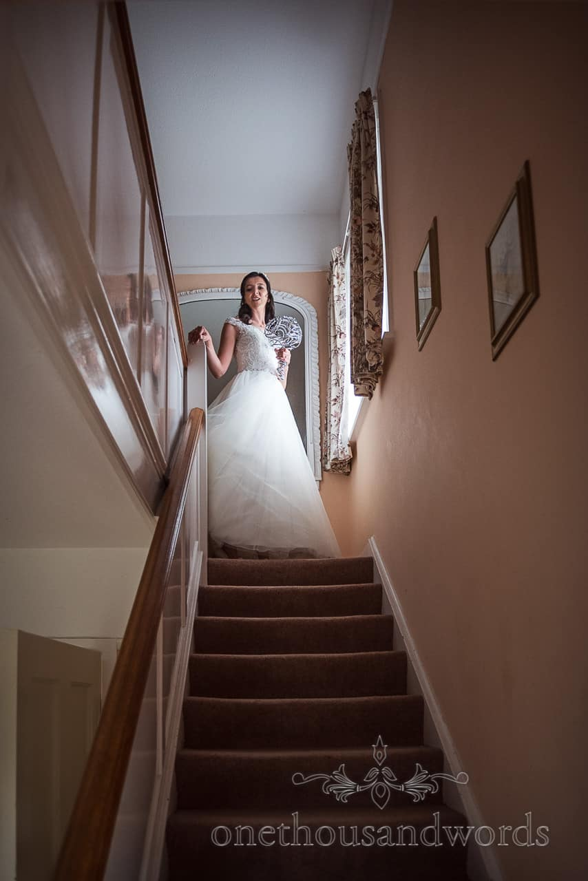 Bride stands atop staircase during Swanage wedding morning