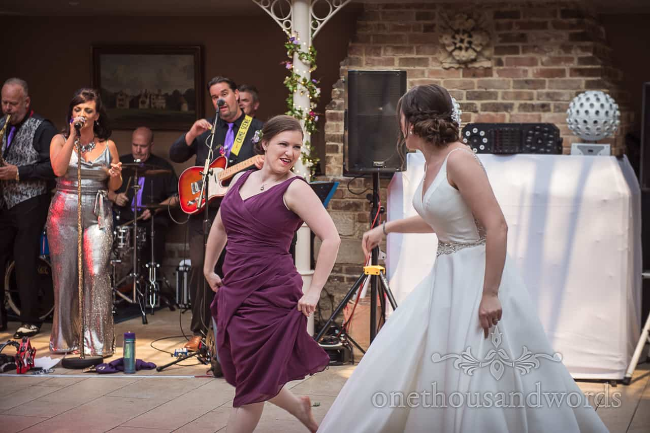Bride and bridesmaid dance Flamenco style to wedding band at Athelhampton House
