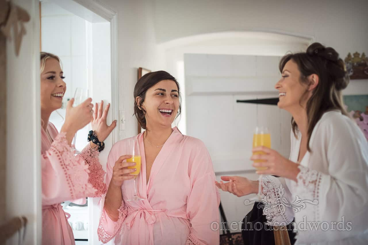 Bride and bridesmaids wearing dressing gowns laugh at a joke during wedding morning preparation photographs
