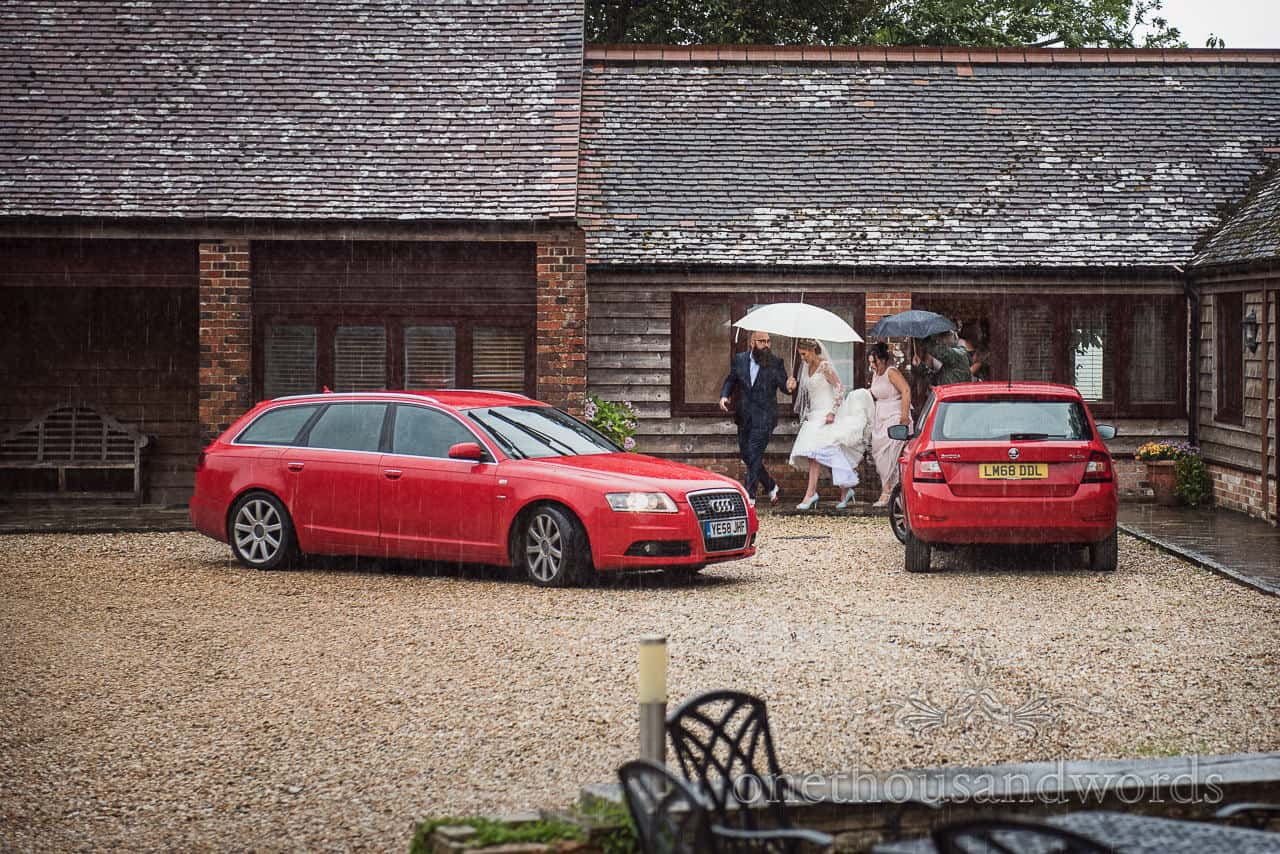 Bride and bridesmaids leave Kingston Country Courtyard bridal suite under umbrellas in the rain with red cars