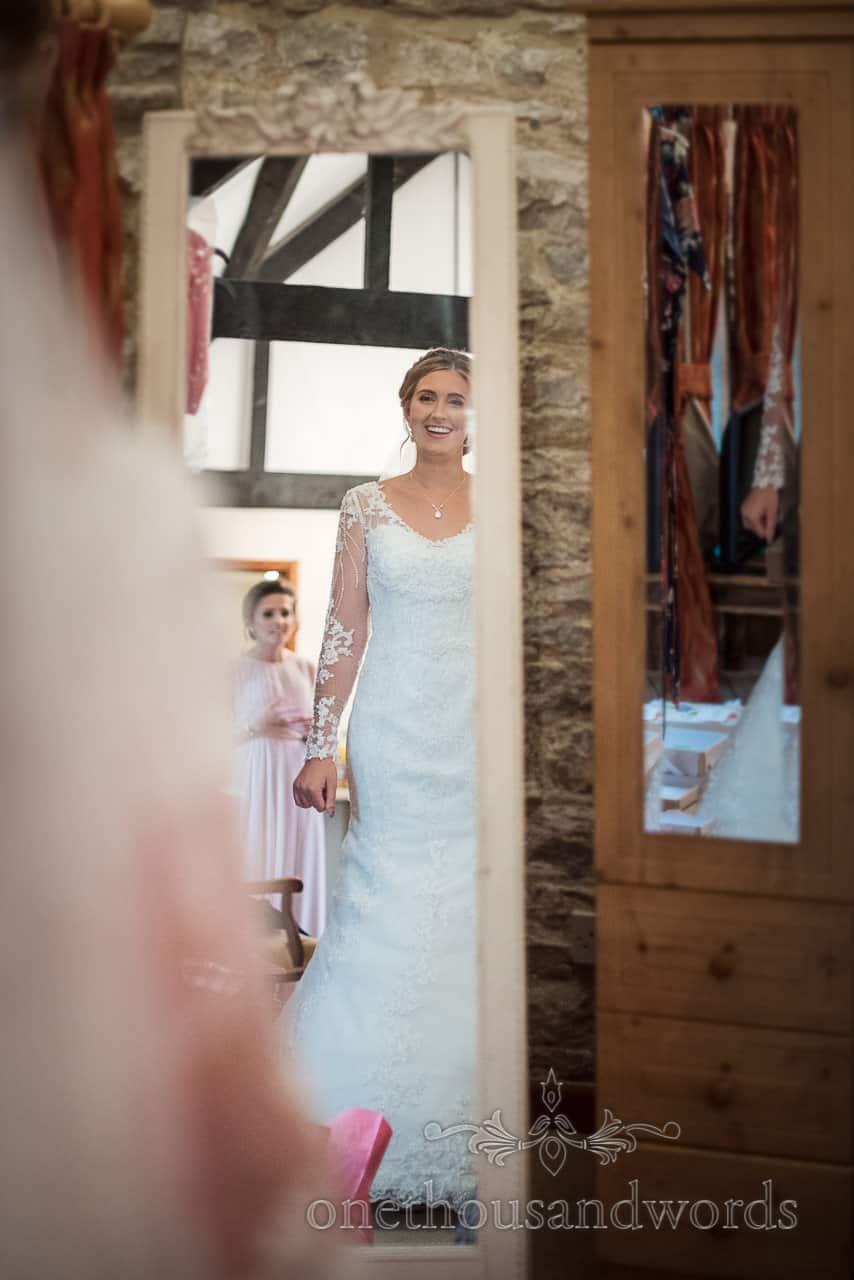 Smiling bride in white wedding dress checks her reflection in full length mirror from Kingston barn wedding photographs