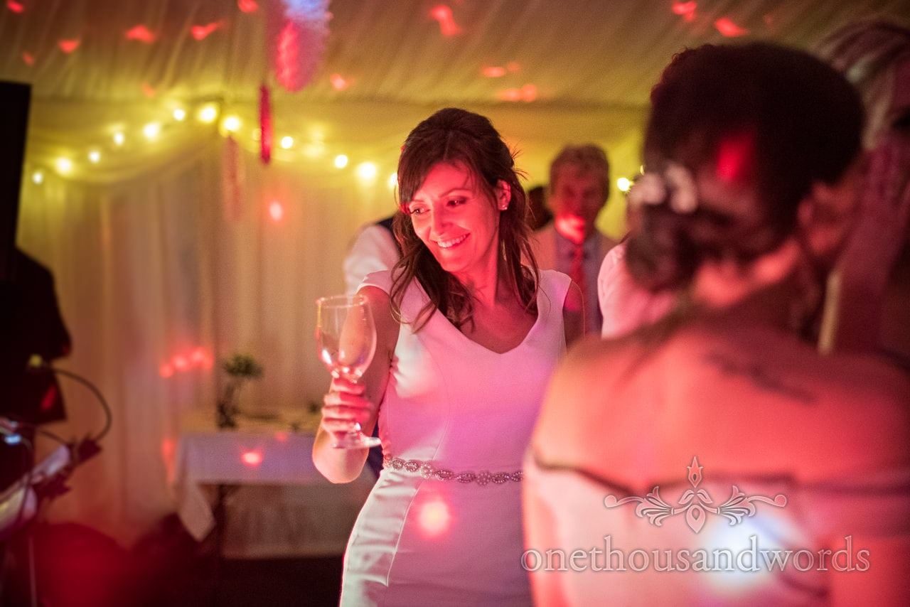 Bride lit with pink disco lights dances with glass in hand in wedding marquee photograph by one thousand words wedding photography
