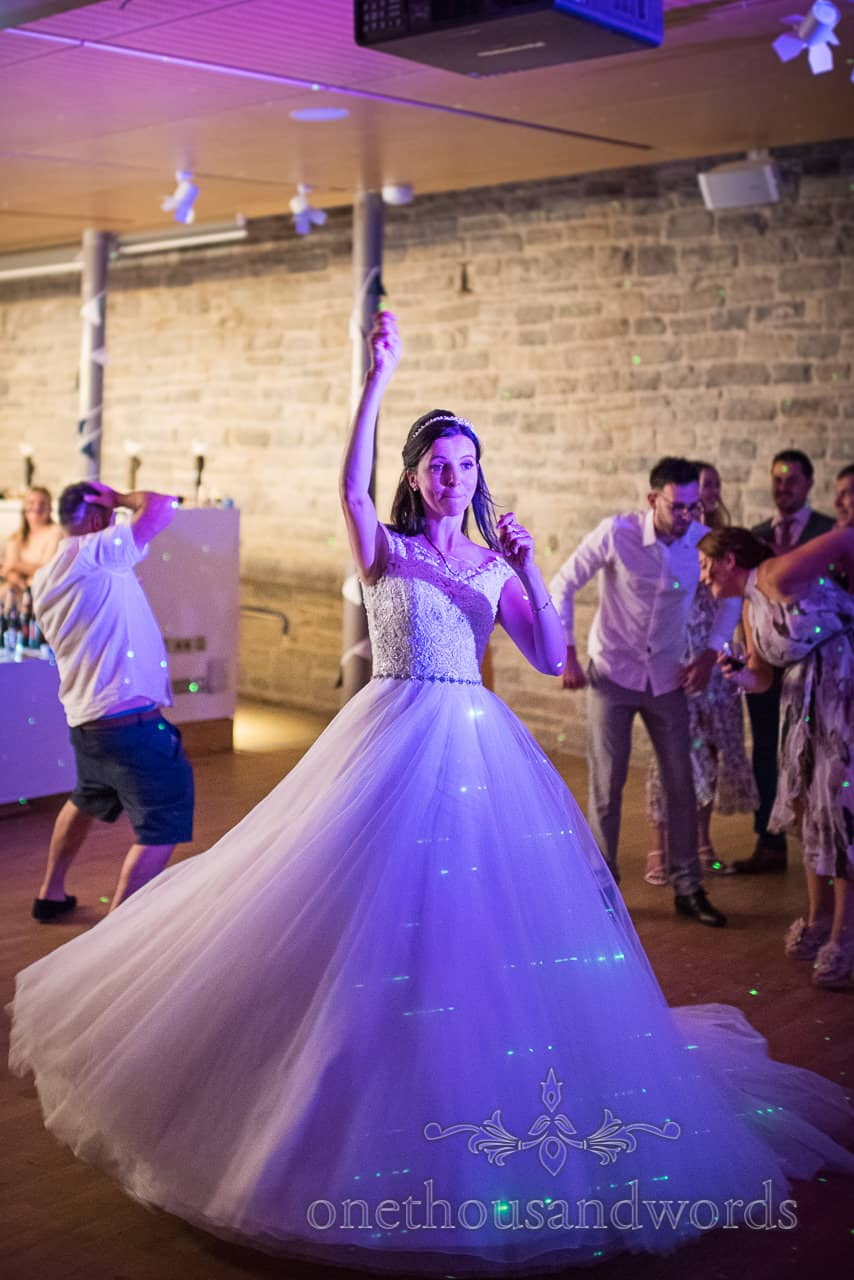 Bride dances with her hand in the air illuminated with blue lights and green lazers surrounded by dancing wedding guests