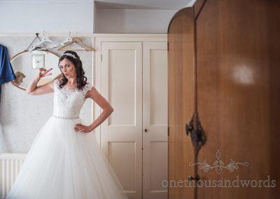 Bride in dress strikes fun pose during wedding morning in Swanage