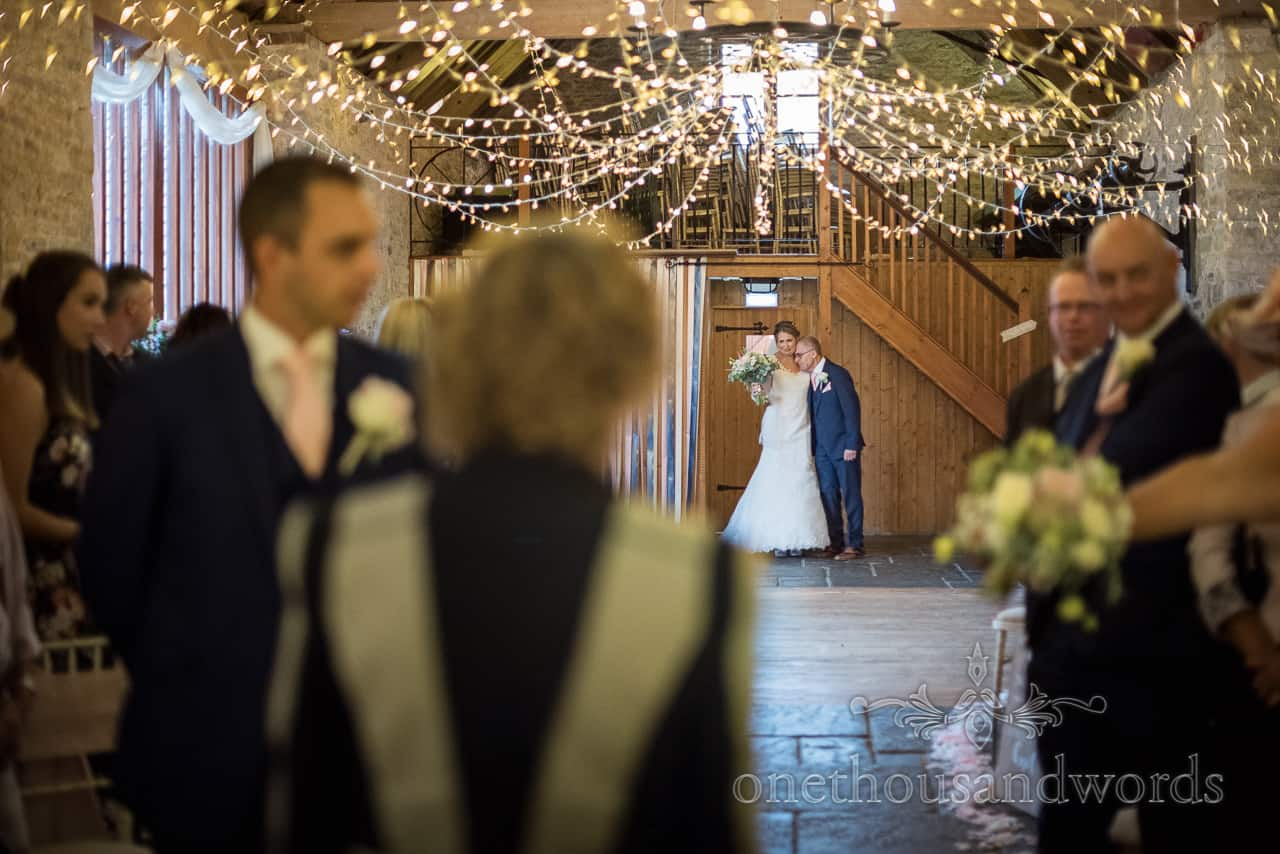 Bride hugs her father as she makes her entrance under fairy lights to ceremony at Kingston barn wedding photographs